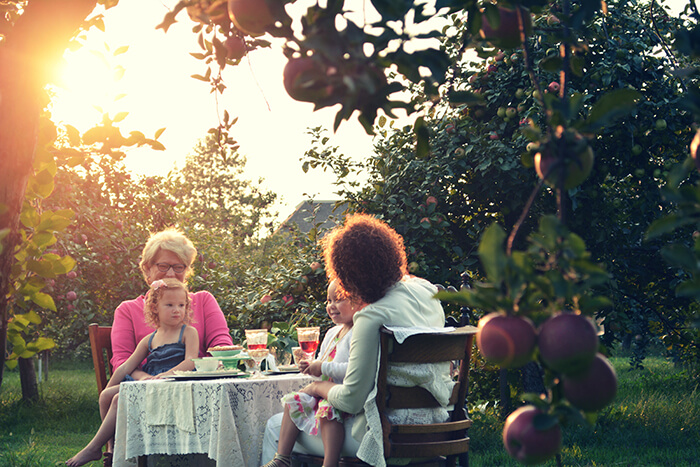 Outdoor scene featuring multiple generations of women around a table